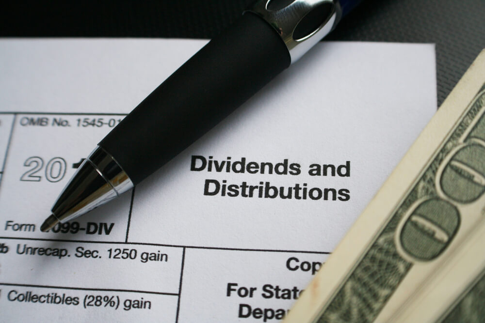 image of an investing dividends and distributions document, with pen and dollar bill on top of it